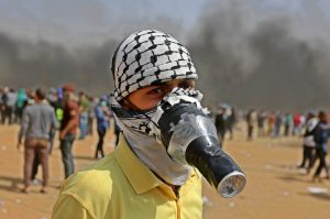a Palestinian protester covers his face to protect himself from tear gas during clashes with Israeli security forces following a protest, on the Gaza-Israel border, in Khan Younis