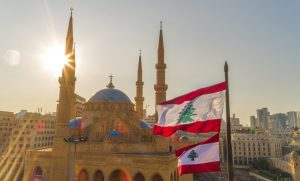 Beirut, Lebanon 2019 : drone shot of Martyr square, showing the Lebanese flag in foreground  along with Mohammad Al Amine Mosque and st. George Church in the background, during the Lebanese revolution